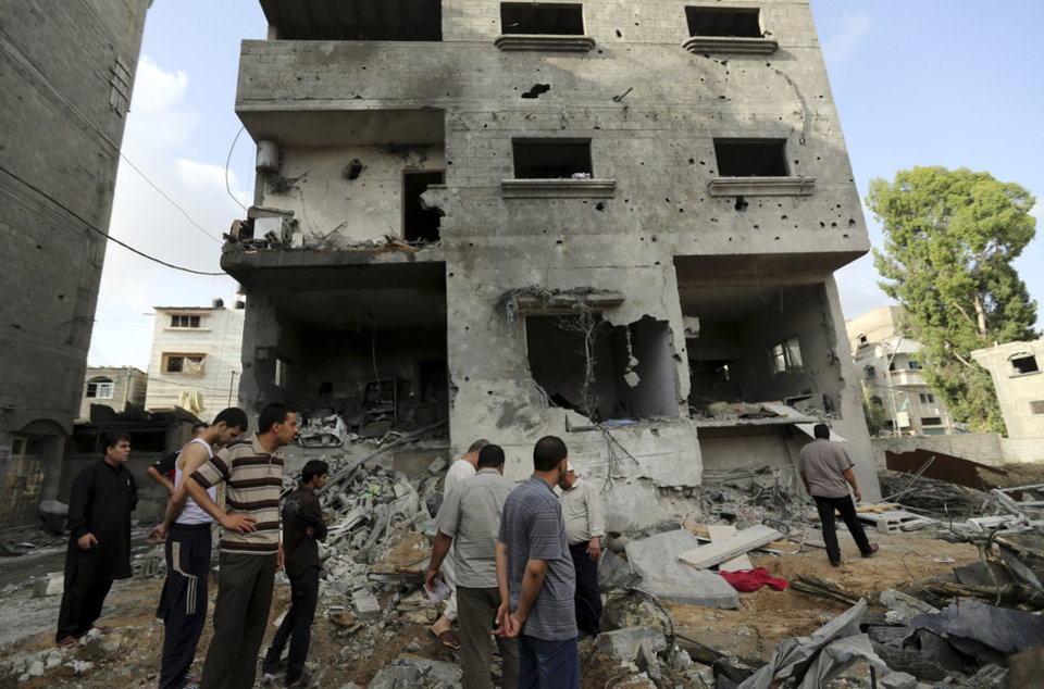 Photo - Palestinians gather outside the damaged house of Gaza's police chief Taysir al-Batsh after it was hit by an Israeli missile strike in Gaza City, Sunday, July 13, 2014. The strike that hit the home and damaged a nearby mosque as evening prayers ended Saturday, killed at least 18 people, wounded 50 and left some people believed to be trapped under the rubble, said Palestinian Health Ministry official Ashraf al-Kidra. (AP Photo/Hatem Moussa)