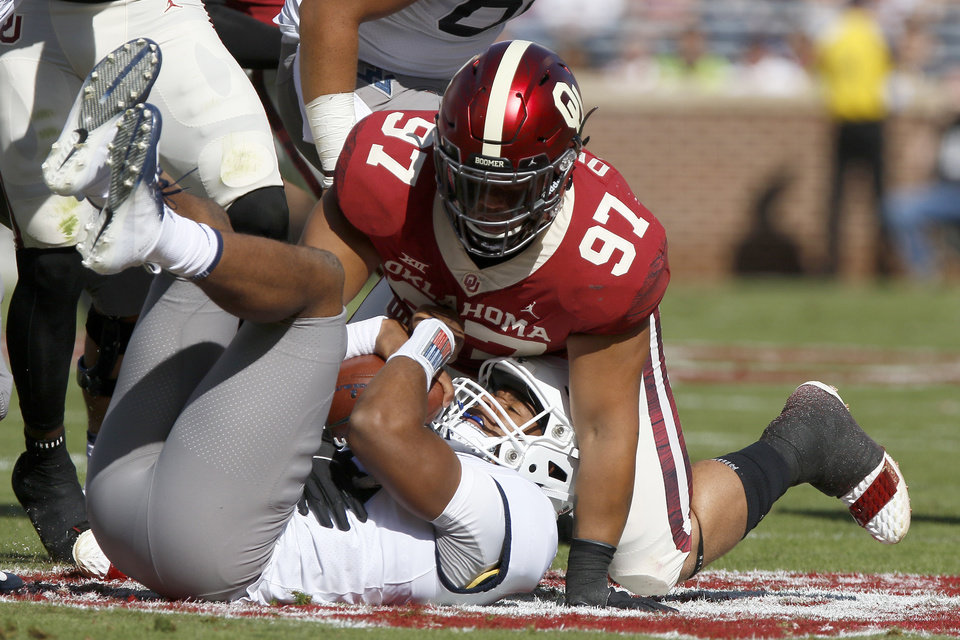 Photo - Oklahoma's Marquise Overton (97) brings down West Virginia's Trey Lowe III (10) during a college football game between the University of Oklahoma Sooners (OU) and the West Virginia Mountaineers at Gaylord Family-Oklahoma Memorial Stadium in Norman, Okla, Saturday, Oct. 19, 2019. Oklahoma won 52-14. [Bryan Terry/The Oklahoman]