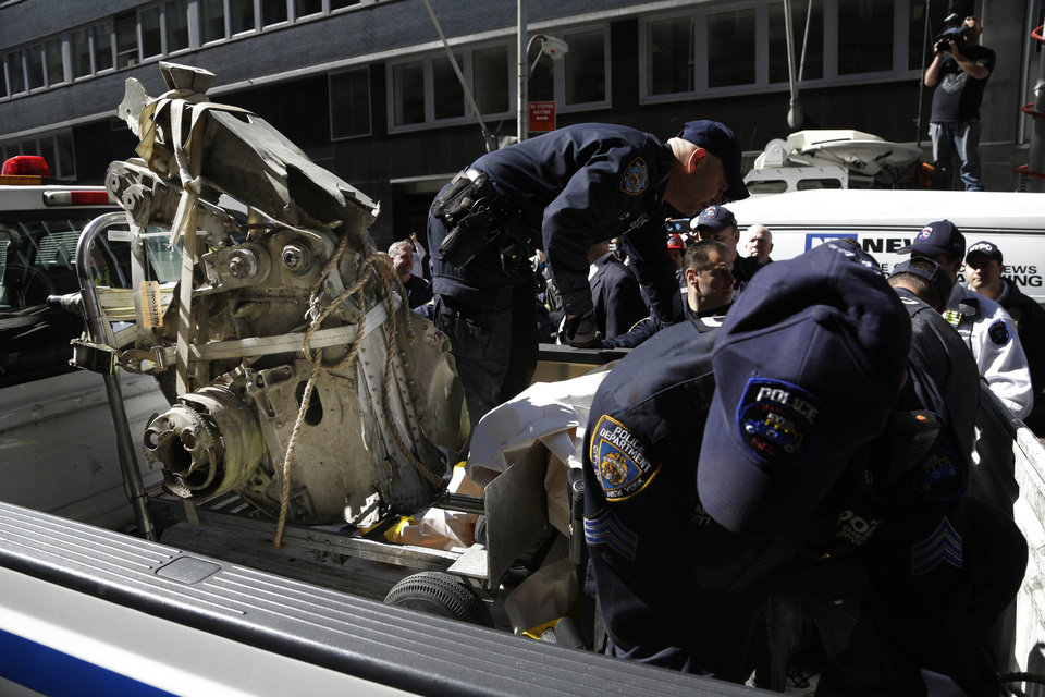 Photo - Officials load a plane part that was discovered wedged between an apartment building and a mosque into a truck in New York, Wednesday, May 1, 2013. Authorities believe the plane part is from one of the two hijacked airliners that brought down the trade center on Sept. 11, 2001. (AP Photo/Seth Wenig)