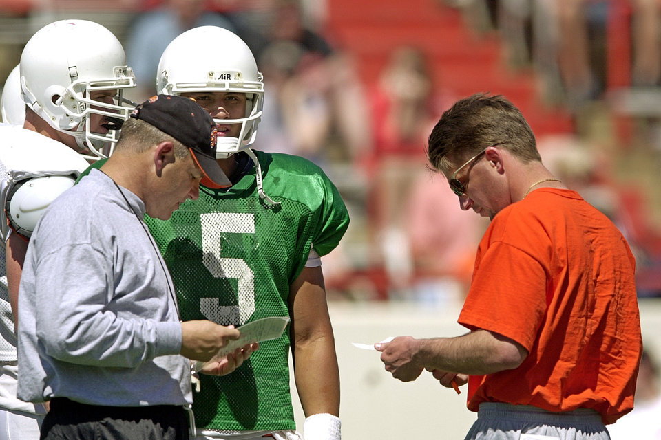 OSU SPRING PRACTICE: Oklahoma State head coach Les Miles (left) and offensive coordinator Mike Gundy (right) talk to quarterback Aso Pogi (middle) during the Orange and White football scrimmage at Lewis Field in Stillwater Saturday. Staff photo by Nate Billings.