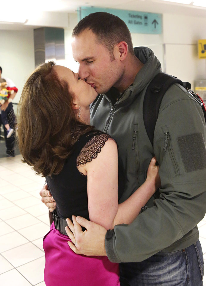 Photo - Angela and David Schnabel reunite at Will Rogers Airport Tuesday afternoon, Feb. 12, 2013. Angela surprised her husband with a new look from her Mood