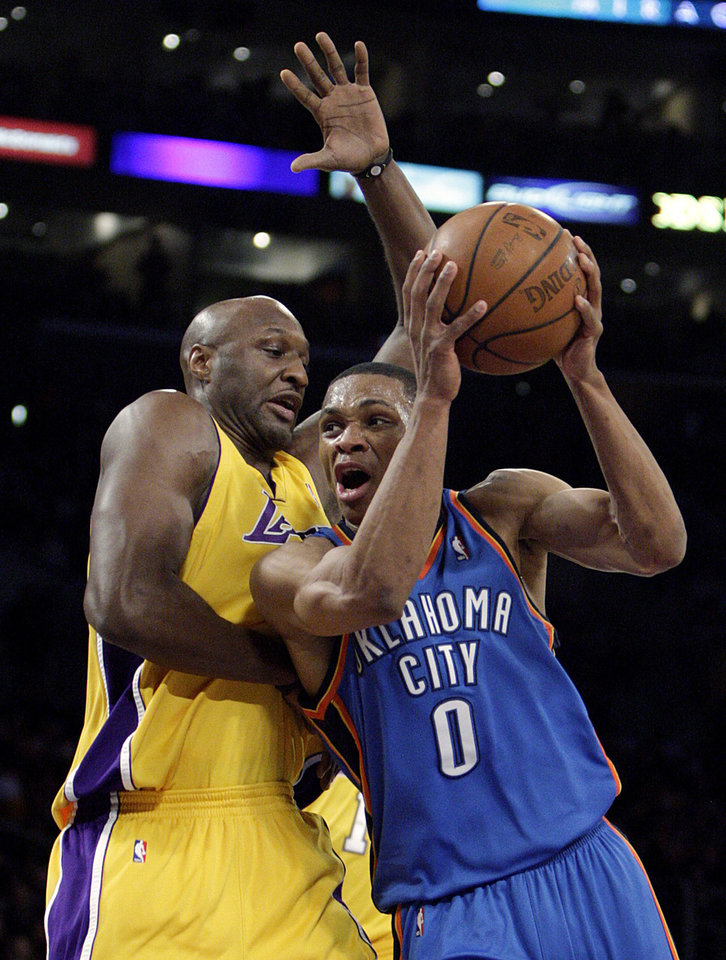 Photo - Oklahoma City Thunder's Russell Westbrook, right, is pressured by Los Angeles Lakers' Lamar Odom during the first half of an NBA basketball game in Los Angeles, Tuesday, Dec. 22, 2009. (AP Photo/Jae C. Hong) ORG XMIT: LAS105
