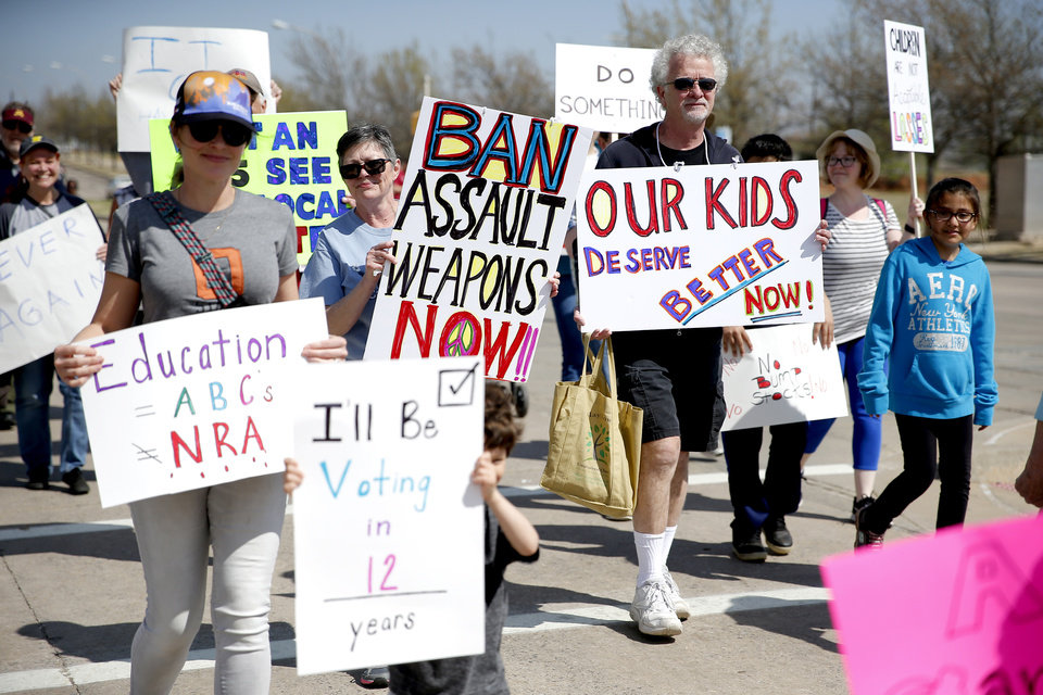Photo -  People carry signs as they walk south Saturday on Lincoln Boulevard toward the state Capitol. [Photo by Sarah Phipps, The Oklahoman]
