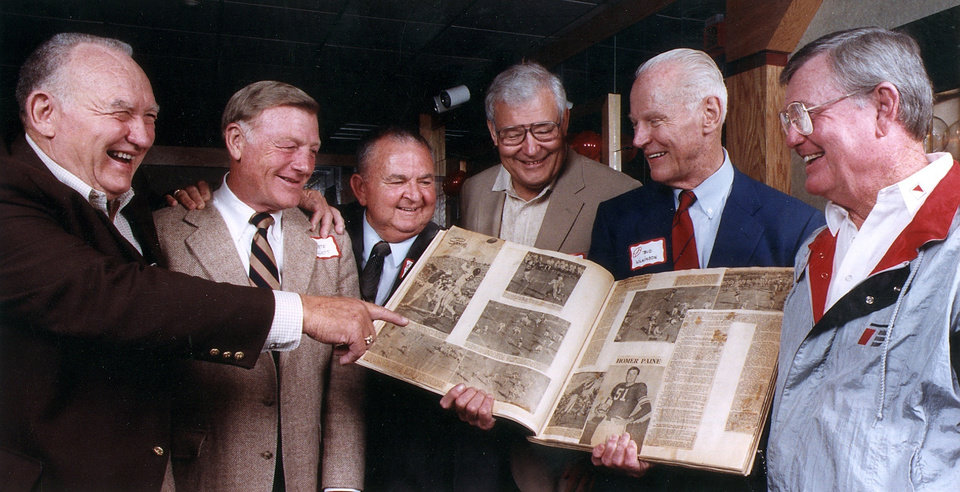 Photo - Looking over a scrapbook at the 1949 University of Oklahoma football team reunion in 2000, from left, Stan Wost, Pete Elliot, Dee Andros, Jim Owens, Bud Wilkinson and Darrell Royal. OKLAHOMAN ARCHIVE PHOTO