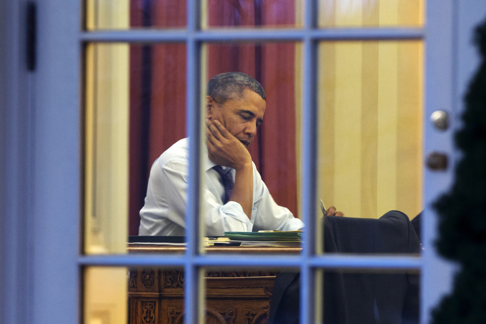 Photo - President Barack Obama works at his desk in the Oval Office of the White House in Washington, Monday, Jan. 27, 2014, ahead of Tuesday night's State of the Union speech. (AP Photo/Jacquelyn Martin)
