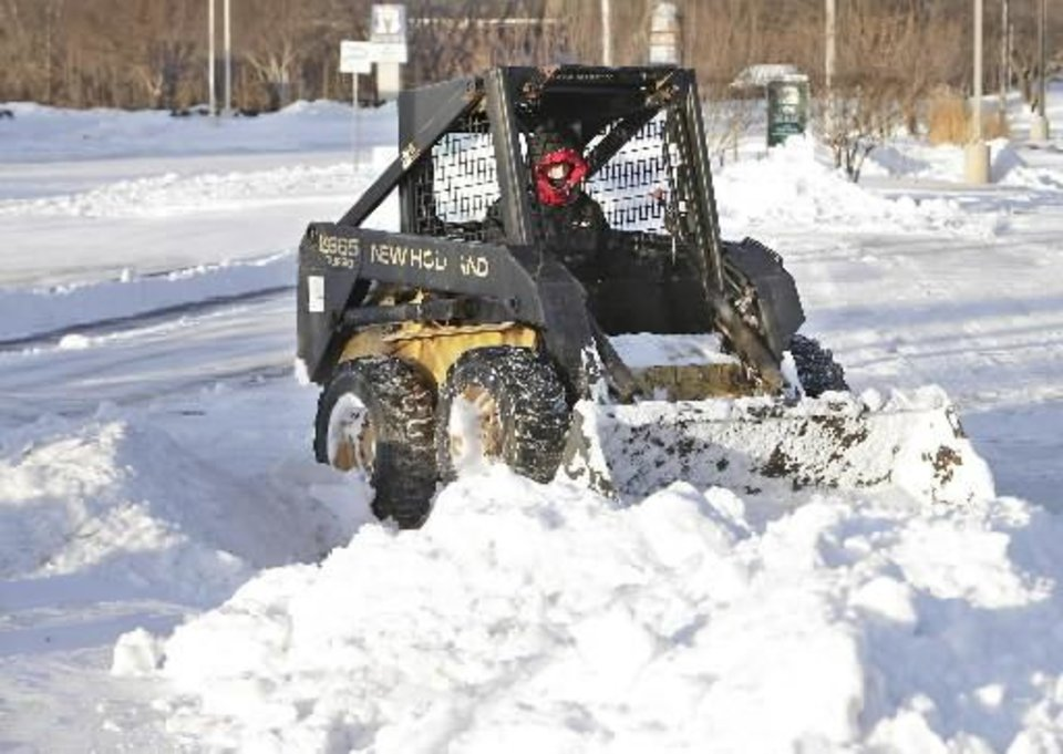 Photo - Rick Hinds clears a parking lot at Edmond Road and Santa Fe in Edmond, Wednesday, February 2, 2011. Hinds said he stared his day at 7:00 A.M. after working all day yesterday. Photo by David McDaniel,