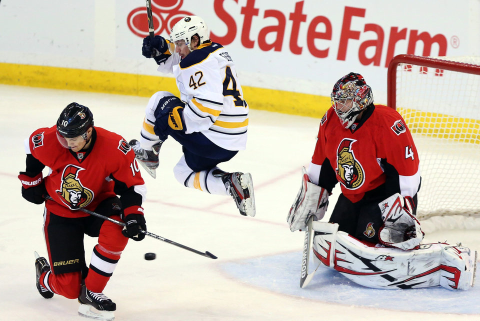 Buffalo Sabres\' Nathan Gerbe (42) jumps as he screens a shot on Ottawa Senators goaltender Craig Anderson (41) as Mike Lundin (10) watches during the first period of their NHL hockey game, Tuesday, Feb. 12, 2013, in Ottawa, Ontario. (AP Photo/The Canadian Press, Fred Chartrand)