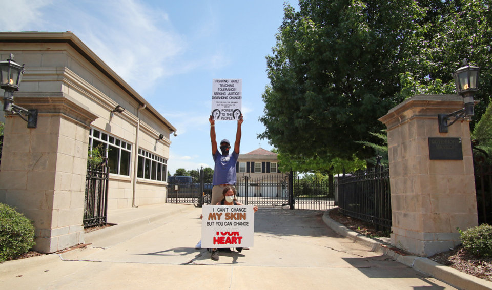 Photo - People hold signs in the drive to the Governor's Mansion on NE 23rd at a 1,000 brothers and sisters in arms for second amendment walk by predominantly black men and women to advocate for their second amendment rights, Saturday, June 20, 2020. [Doug Hoke/The Oklahoman]