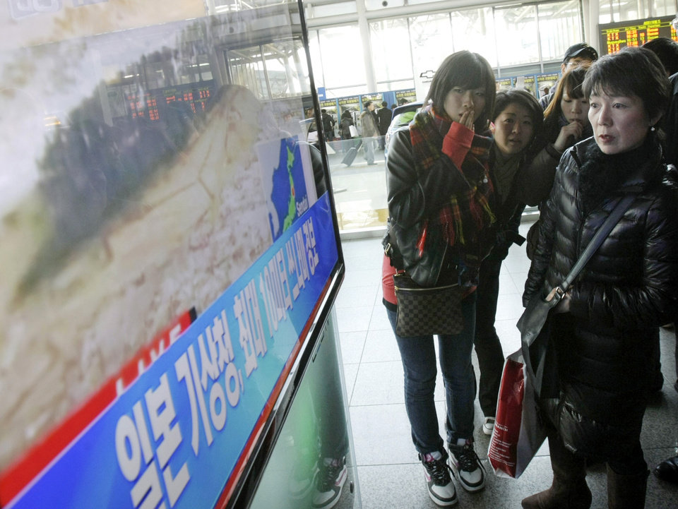 Photo - Japanese tourists watch a TV news program about a strong earthquake hitting their country at Seoul Railway Station in Seoul, South Korea, Friday, March 11, 2011. The letters read