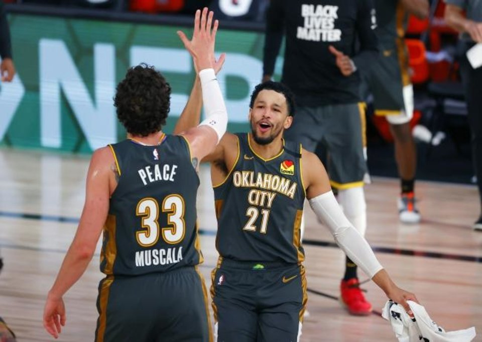 Photo -  Andre Roberson (21) celebrates with Mike Muscala (33) during a game against the Heat on Aug. 12 in Lake Buena Vista, Fla. [Kevin C. Cox/Pool Photo via AP]