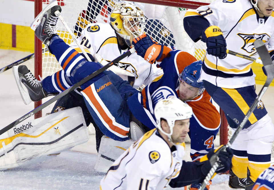 Nashville Predators goalie Carter Hutton (30) is crashed into by Edmonton Oilers Taylor Hall (4) during second period NHL hockey action in Edmonton, Canada, Sunday, Jan. 26, 2014. (AP Photo/The Canadian Press, Jason Franson)
