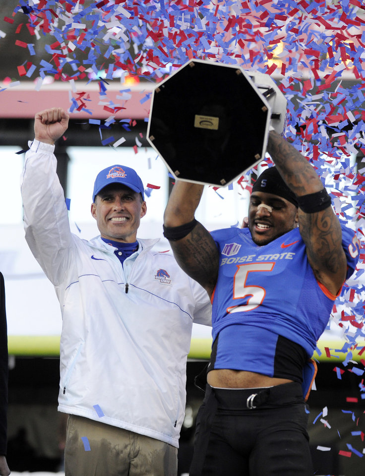 Photo - FILE - In this Dec. 22, 2012 file photo, Boise State coach Chris Peterson, left, gestures as cornerback Jamar Taylor holds the championship trophy after the MAACO Bowl NCAA college football game against Washington, in Las Vegas. A person familiar with the decision tells The Associated Press that Petersen has agreed to leave Boise State and be the football coach at Washington.  The person told spoke on the condition of anonymity Friday morning, Dec. 6, 2013,  because the hiring had not been announced by Washington.  (AP Photo/David Becker)