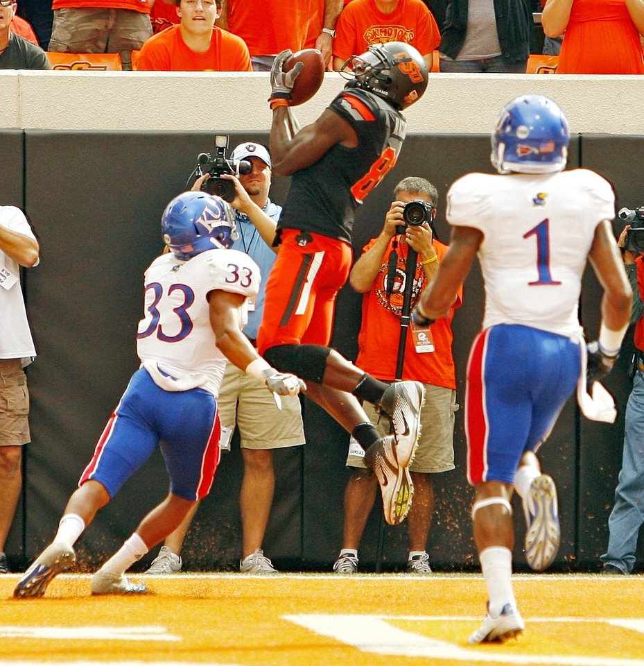 Photo - Oklahoma State's Justin Blackmon (81) scores between Kansas' Tyler Patmon (33) and Lubbock Smith (1) during a college football game between the Oklahoma State University Cowboys (OSU) and the University of Kansas Jayhawks (KU) at Boone Pickens Stadium in Stillwater, Okla., Saturday, Oct. 8, 2011 Photo by Steve Sisney, The Oklahoman