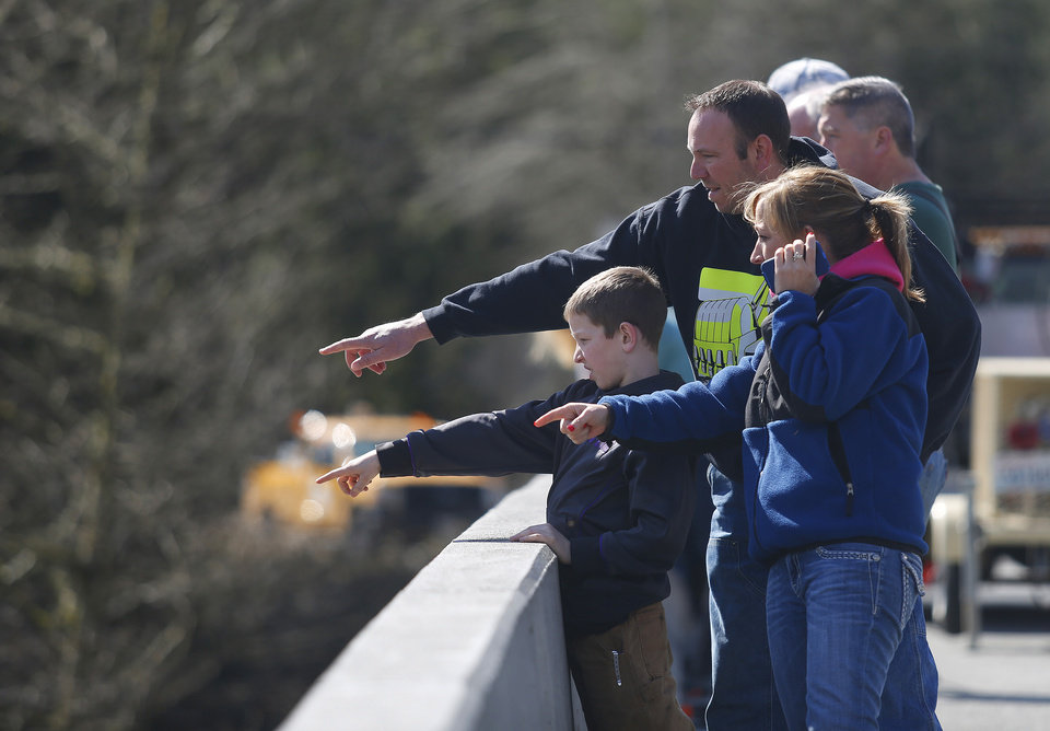 Photo - Residents watch as debris comes down the Stillaguamish River from the Whitman Road bridge east of Oso, Wash.,  Sunday, March 23, 2014. (AP Photo /The Herald, Mark Mulligan)