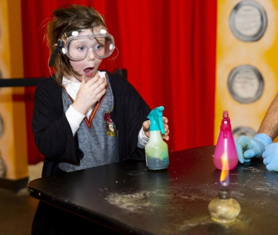 Photo -  A child shows surprise while participating in a hands-on activity during a previous wizard-themed Late Nite Lab at Science Museum Oklahoma. [PROVIDED]
