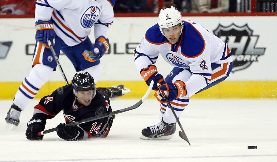 Photo - Carolina Hurricanes' Nathan Gerbe (14) loses his edge and the puck to Edmonton Oilers' Taylor Hall (4) during the first period of an NHL hockey game in Raleigh, N.C., Sunday, March 16, 2014. (AP Photo/Karl B DeBlaker)