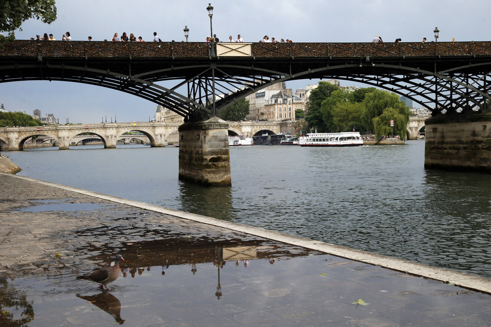 Photo - A wooden repaired section is seen, centre, on the Pont des Arts bridge after a chunk of fencing with thousands of locks fell off under their weight in Paris, Monday, June 9, 2014. The thousands of locks that cling like barnacles to the Pont des Arts in Paris have become a symbol of danger, rather than love, after a chunk of fencing fell off under their weight. The fencing tumbled late Sunday on the pedestrian bridge, which crosses the Seine. (AP Photo/Francois Mori)