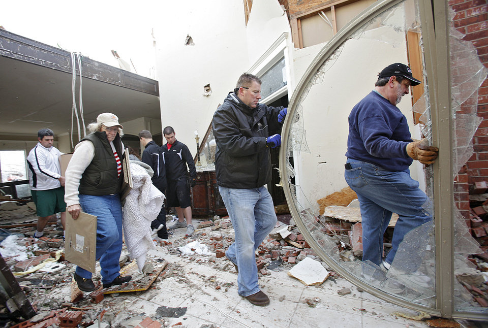 Friends, family and neighbors help Ray Cales, far right, clear debris from his home in the Oak Tree addition on Wednesday, Feb. 11, 2009, after a tornado hit the area on Tuesday in Edmond, Okla.  PHOTO BY CHRIS LANDSBERGER, THE OKLAHOMAN