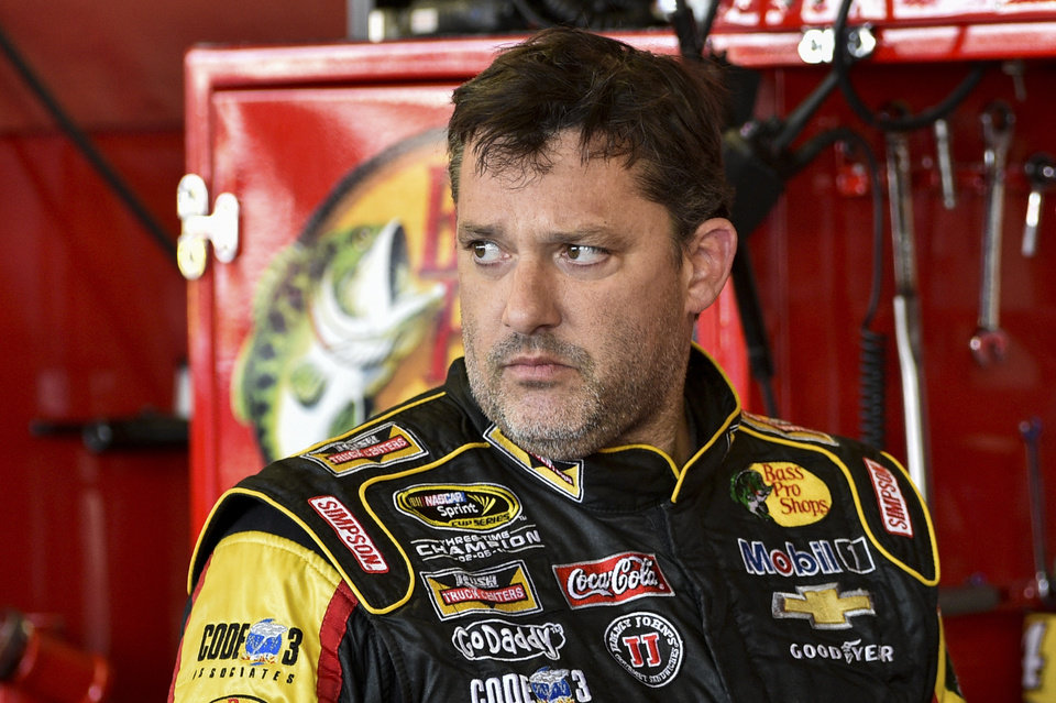 Photo - In this Friday, Aug. 8, 2014 photograph, Tony Stewart stands in the garage area after a practice session for Sunday's NASCAR Sprint Cup Series auto race at Watkins Glen International, in Watkins Glen N.Y.  Stewart struck and killed Kevin Ward Jr., 20, a sprint car driver who had climbed from his car and was on the track trying to confront Stewart during a race at Canandaigua Motorsports Park in upstate New York on Saturday night. Ontario County Sheriff Philip Povero said his department's investigation is not criminal and that Stewart was