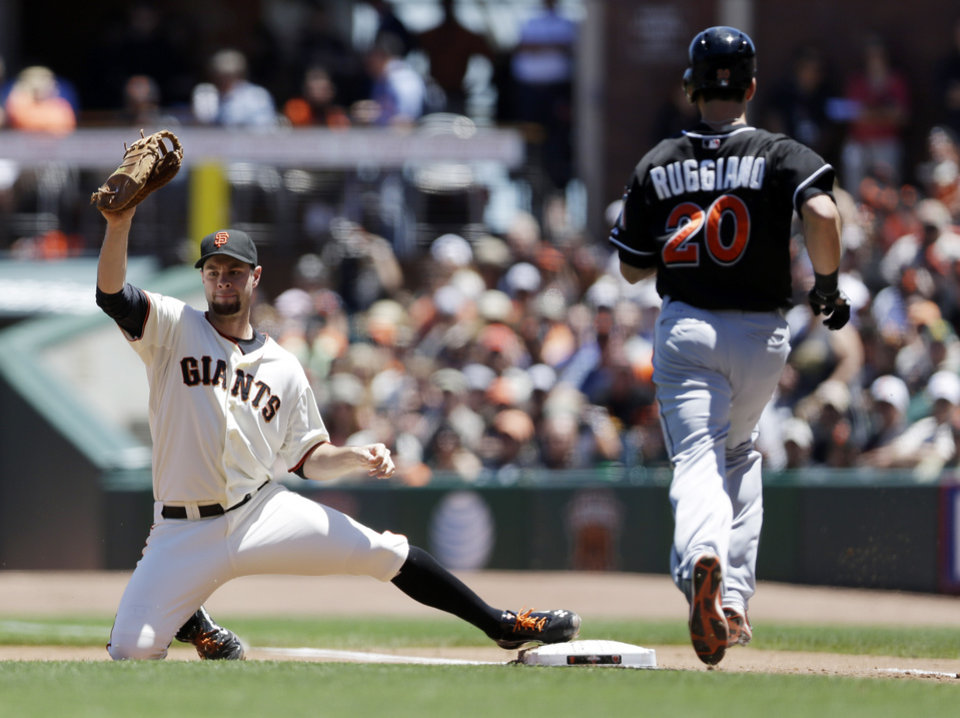 Photo - San Francisco Giants first baseman Brandon Belt, left, scoops a low throw from starting pitcher Barry Zito to put out Miami Marlins' Justin Ruggiano (20) at first base during the third inning of a baseball game on Saturday, June 22, 2013, in San Francisco. (AP Photo/Marcio Jose Sanchez)