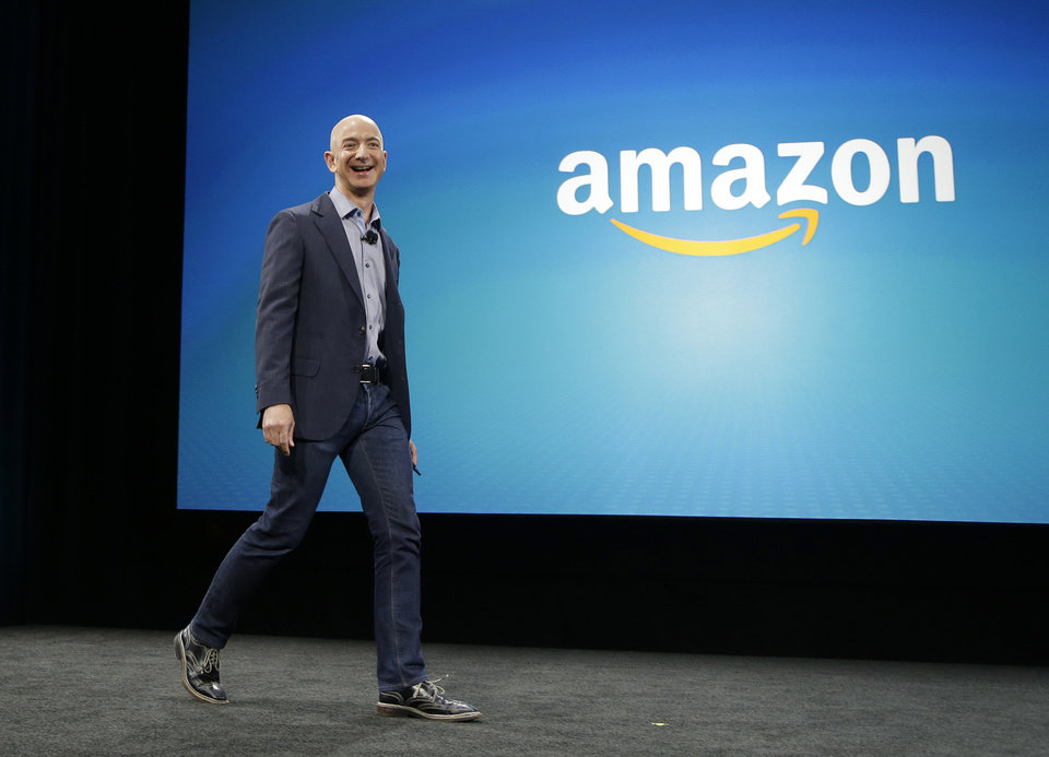 Photo - Amazon CEO Jeff Bezos walks on stage for the launch of the new Amazon Fire Phone, Wednesday, June 18, 2014, in Seattle. (AP Photo/Ted S. Warren)