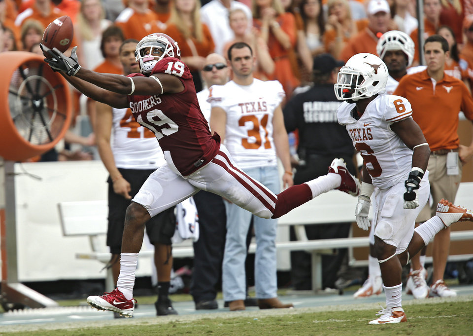 Photo - OU's Justin Brown (19) has a pass go off his finger tips in front of UT's Quandre Diggs (6) during the Red River Rivalry college football game between the University of Oklahoma (OU) and the University of Texas (UT) at the Cotton Bowl in Dallas, Saturday, Oct. 13, 2012. Photo by Chris Landsberger, The Oklahoman