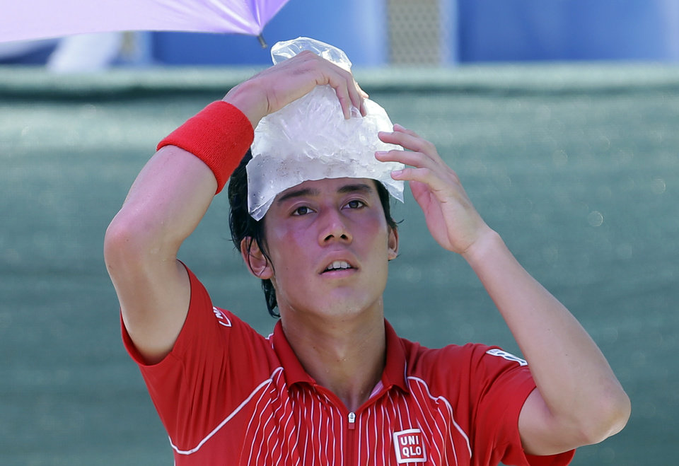 Photo - Kei Nishikori, of Japan, cools off between sets during the match against David Ferrer, of Spain, at the Sony Open Tennis tournament in Key Biscayne, Fla., Tuesday, March 25, 2014. (AP Photo/Alan Diaz)