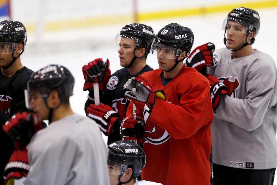 New Jersey Devils right wing Steve Bernier (18) stands with teammates as they listen to head coach Peter DeBoer talk to them during the team's first official practice since the NHL hockey lockout ended, Sunday, Jan. 13, 2013, in Newark, N.J. (AP Photo/Julio Cortez)