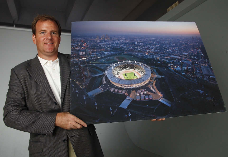 Photo - Todd Gralla, an architect with Populous in Norman, poses for a photo in the OPUBCO studio, Monday, July 23, 2012.  He is holding a photo of the Olympic Stadium in London that his company designed.  Photo by Garett Fisbeck, The Oklahoman  Garett Fisbeck - The Oklahoman