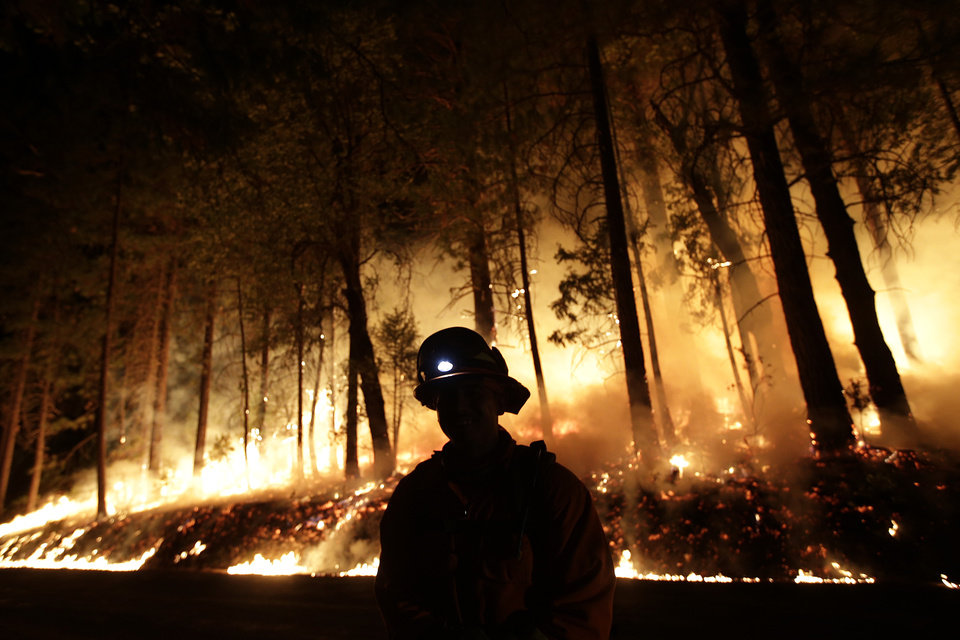 Photo - A firefighter watches for spot fires during a burnout operation while battling the Rim Fire near Yosemite National Park, Calif., on Sunday, Aug. 25, 2013. Fire crews are clearing brush and setting sprinklers to protect two groves of giant sequoias as a massive week-old wildfire rages along the remote northwest edge of Yosemite National Park. (AP Photo/Jae C. Hong)