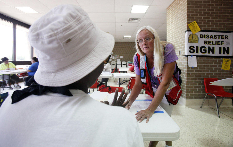 Red Cross volunteer Tina Spencer, of Utah, works with a tornado victim on required relief paperwork at Westmoore High School on Wednesday. Photo by Aliki Dyer, The Oklahoman. <strong>Aliki Dyer</strong>