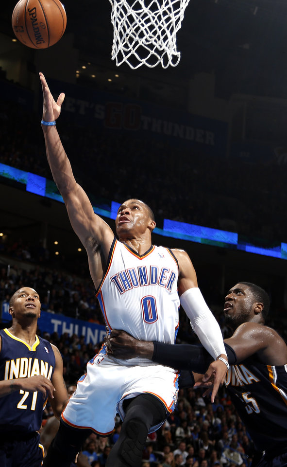 Oklahoma City's Russell Westbrook (0) shoots a lay up as he is fouled by Roy Hibbert (55) during the NBA game between the Oklahoma City Thunder and the Indiana Pacers at the Chesapeake Energy Arena, Sunday, Dec. 8, 2013. Photo by Sarah Phipps, The Oklahoman