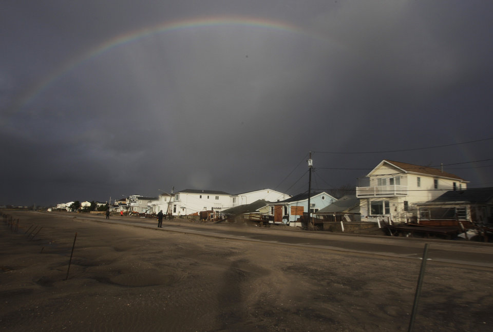 Photo -   A rainbow forms over Breezy Point in the New York City borough of Queens, in the aftermath of superstorm Sandy, Tuesday, Oct. 30, 2012, in New York. The fire destroyed between 80 and 100 houses Monday night in the flooded neighborhood. (AP Photo/Frank Franklin II)