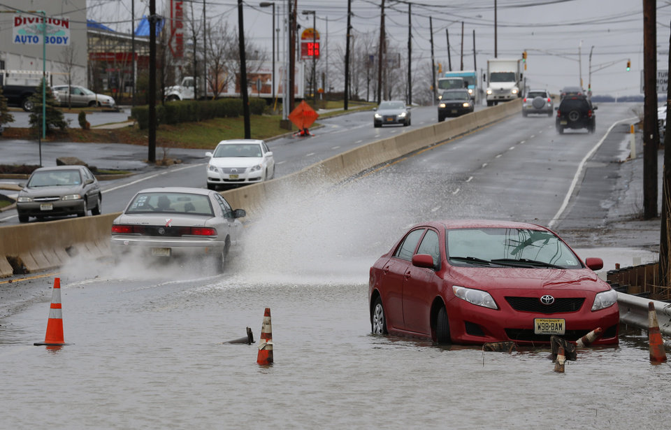 Photo - A vehicle stands abandoned facing in the wrong direction as traffic flows around  floodwaters on Route 35 in Keyport, N.J., where an overnight storm caused coastal flooding, Thursday, Dec. 27, 2012. (AP Photo/Julio Cortez)