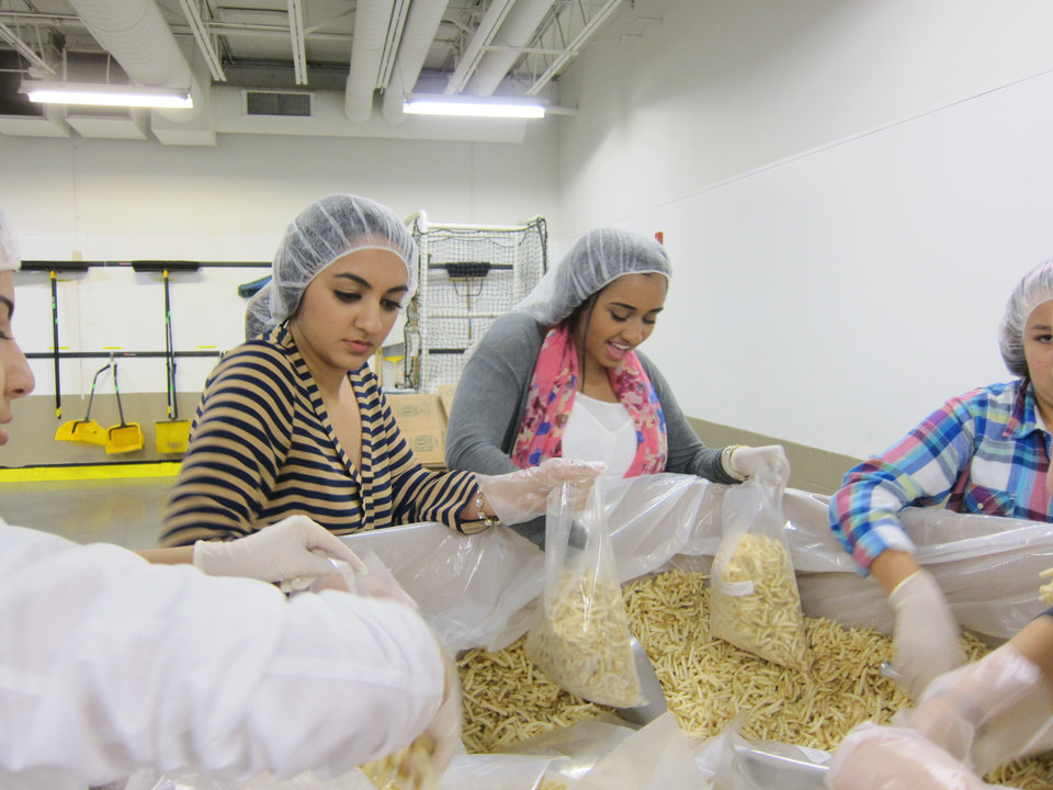 Photo -  Mariyam Kahn and  Sara Iftikhar, both of Tulsa, package frozen french fries during the recent Ramadan Day of Service effort at the Regional Food Bank in Oklahoma City. Photo by Carla Hinton, The Oklahoman