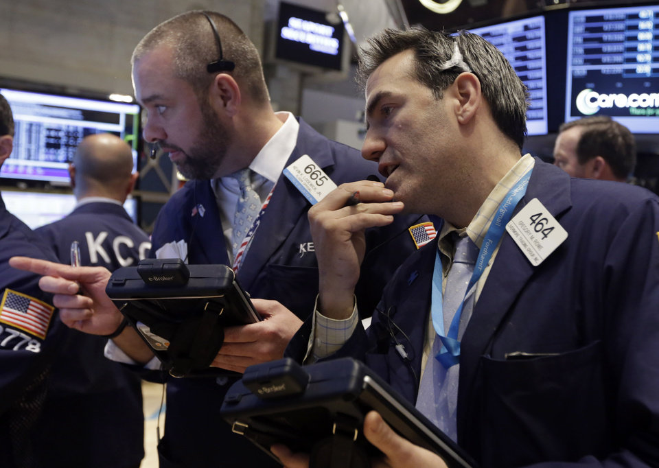 Photo - Traders Kevin Lodewick, left, and Gregory Rowe work on the floor of the New York Stock Exchange, Wednesday, Feb. 26, 2014.  The stock market is little changed as investors pick over more earnings reports from retailers and other U.S. companies. (AP Photo/Richard Drew)