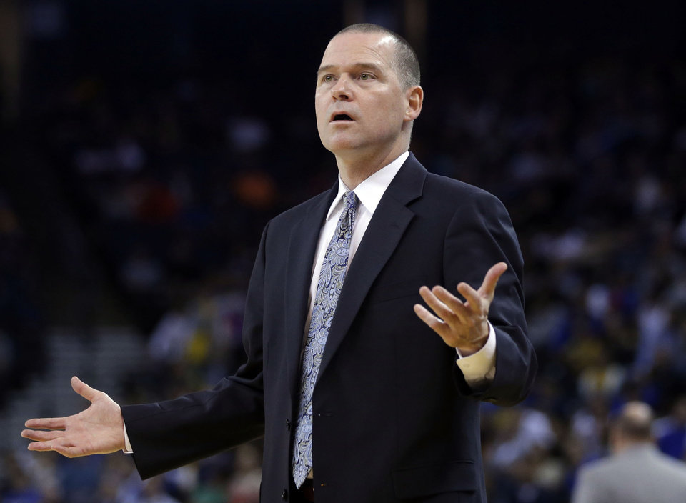 Photo - Sacramento Kings cooach Michael Malone questions a call as his team plays the Golden State Warriors during the first half of an NBA preseason basketball game on Monday, Oct. 7, 2013, in Oakland, Calif. (AP Photo/Marcio Jose Sanchez)