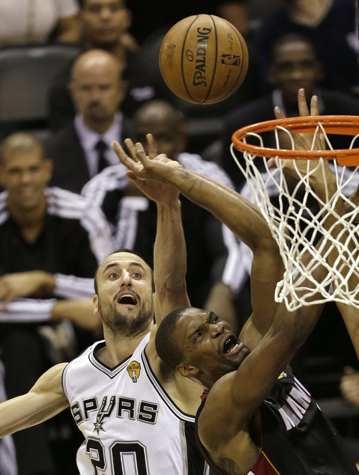 Photo - Miami Heat's Chris Bosh (1) is defended by San Antonio Spurs' Manu Ginobili (20), of Argentina, during the first half at Game 4 of the NBA Finals basketball series, Thursday, June 13, 2013, in San Antonio. (AP Photo/David J. Phillip)