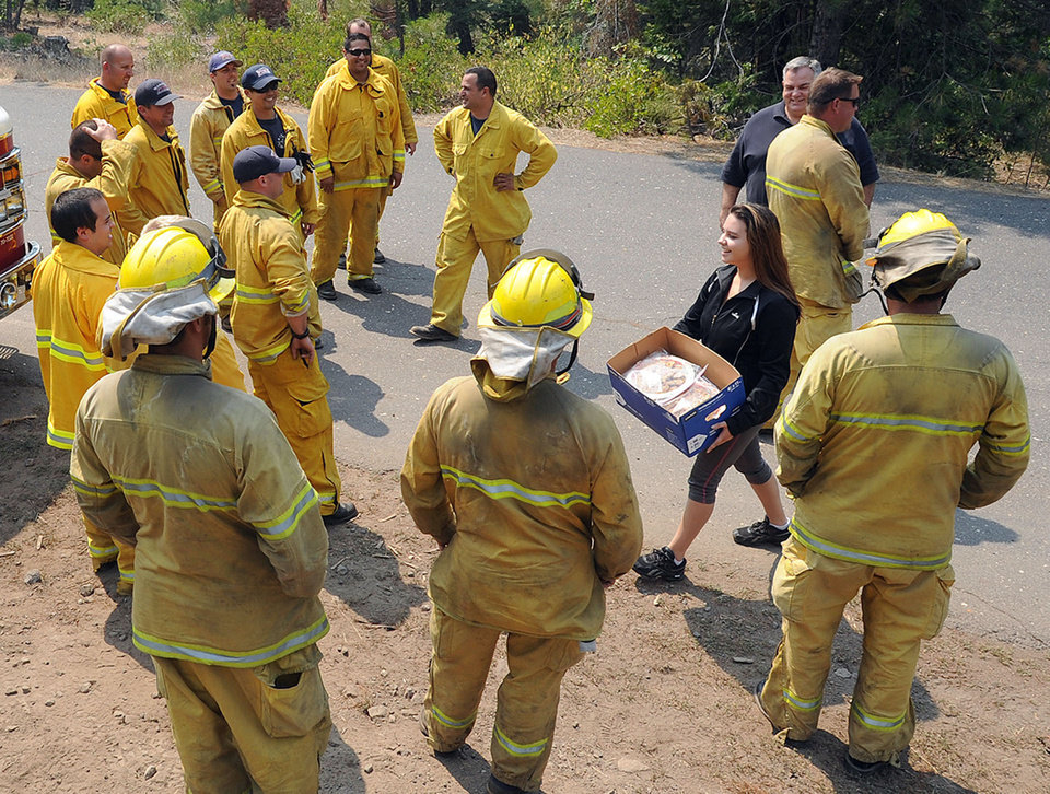 Modesto's Jessy Boonstra, from Ripon Immanuel Christian Reformed Church, carries a box of home baked cookies she brought along with Ripon Fire Chief and San Joaquin County Operational Area Coordinator Dennis Bitters, on a surprise visit to a strike team of San Joaquin County firefighters working along Forest Service road 31 behind Long Barn off of Hwy 108 Wednesday afternoon (08-28-13).  (AP Photo/Elias Funez, The Modesto Bee)  NO SALES, NO MAGS, NO TV, ONLINE AP MEMBERS ONLY