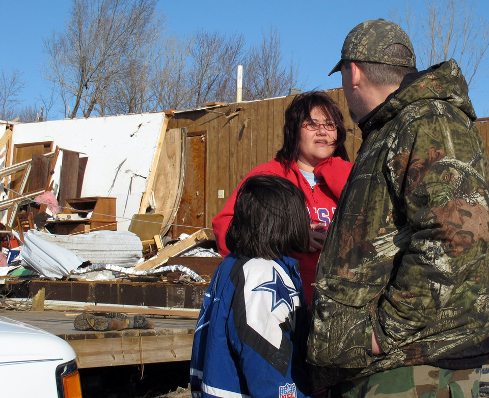 Tammy Woodyard, center, talks to neighbor Grant Hill, right, and his daughter, Talla, about the tornado damage to her father's home behind her, Wednesday, Feb. 29, 2012, in Harveyville, Kan. (AP Photo/John Hanna) ORG XMIT: RPJH104