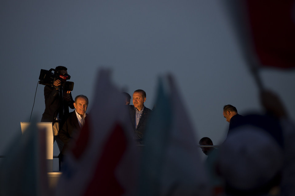 Photo - Prime Minister Recep Tayyip Erdogan, center, who is the front-runner in Turkey's presidential election, waves to the crowd on top of a bus in downtown Istanbul, Turkey, Sunday, Aug. 10, 2014. Turks were voting in their first direct presidential election Sunday _ a watershed event in Turkey's 91-year history, where the president was previously elected by Parliament. Prime Minister Recep Tayyip Erdogan, who has dominated the country's politics for the past decade, is the strong front-runner to replace the incumbent, Abdullah Gul, for a five-year term. (AP Photo/Emilio Morenatti)