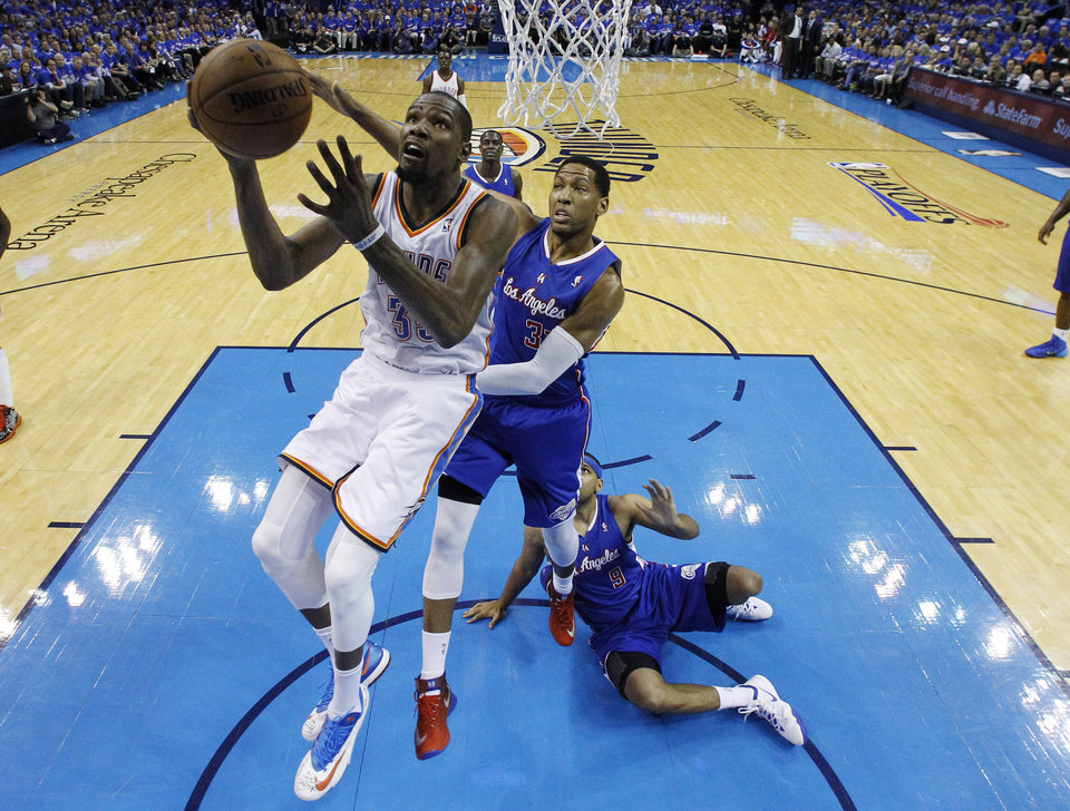 Photo - Oklahoma City Thunder forward Kevin Durant (35) goes up for a shot in front of Los Angeles Clippers forward Danny Granger (33) and forward Jared Dudley (9) in the second quarter of Game 1 of the Western Conference semifinal NBA basketball playoff series in Oklahoma City, Monday, May 5, 2014. (AP Photo/Sue Ogrocki)