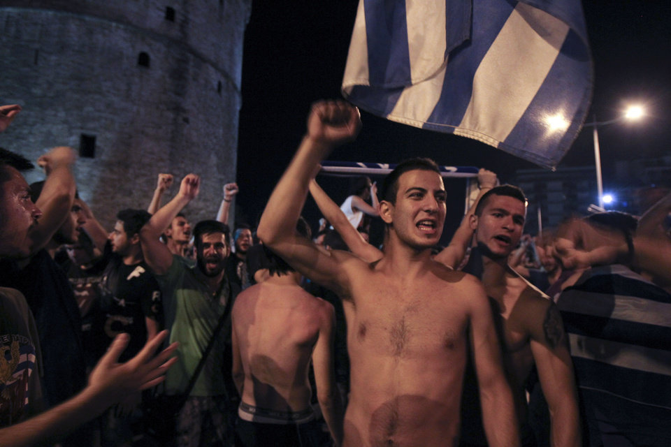 Photo - Greece soccer supporters celebrate their team's win in a World Cup soccer match in front of city's landmark of White Tower, in the northern Greek port of Thessaloniki, on Wednesday, June 25, 2014. Greece won Ivory Coast 2-1 to advance to the round of 16 for the first time in their World Cup history. (AP Photo/Nikolas Giakoumidis)
