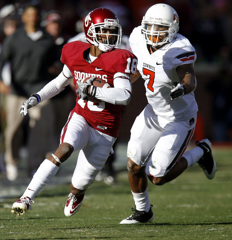 Photo - Oklahoma's Jalen Saunders (18) runs past Oklahoma State's Shamiel Gary (7) after a reception in the Bedlam college football game between the University of Oklahoma Sooners (OU) and the Oklahoma State University Cowboys (OSU) at Gaylord Family-Oklahoma Memorial Stadium in Norman, Okla., Saturday, Nov. 24, 2012. Oklahoma won 51-48. Photo by Bryan Terry, The Oklahoman
