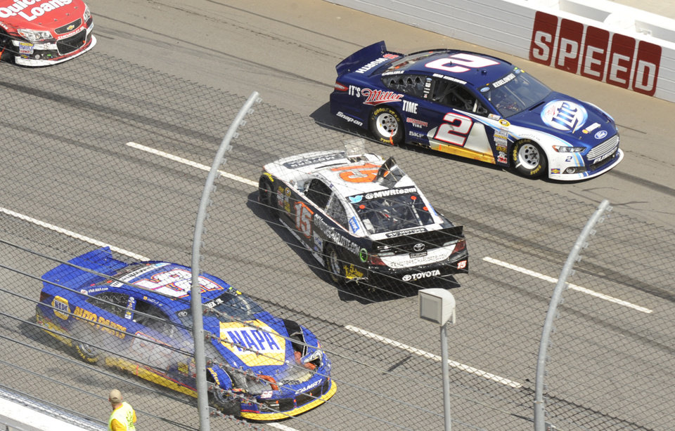 Clint Bowyer (15) spins out in the front stretch as Brad Keselowski (2) and Martin Truex Jr. (56) pass by during the STP 500 NASCAR Sprint Cup series auto race at Martinsville Speedway in Martinsville, Va., Sunday, April 7, 2013. (AP Photo/Don Petersen)