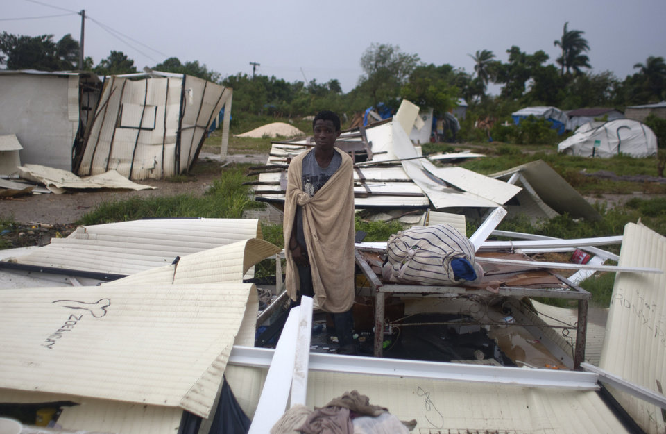 Photo -   A man stands next to his bed after Tropical Storm Isaac destroyed his home and others at a camp set up for people displaced by the 2010 earthquake in Port-au-Prince, Haiti, Saturday, Aug. 25, 2012. Tropical Storm Isaac swept across Haiti's southern peninsula early Saturday, dousing a capital city prone to flooding and adding to the misery of a poor nation still trying to recover from the 2010 earthquake. (AP Photo/Dieu Nalio Chery)