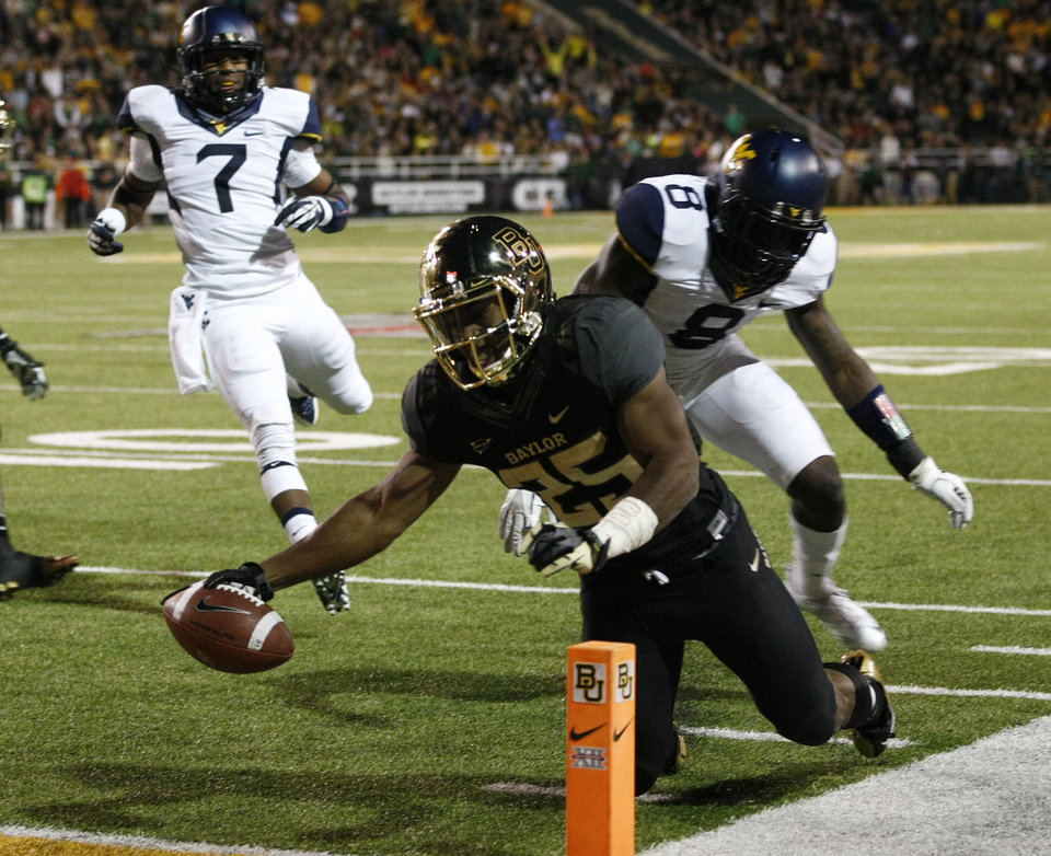 Photo - *Baylor running back Lache Seastrunk (25) scores past West Virginia safety Karl Joseph (8), right, during the first half of an NCAA college football game onSaturday, Oct.  5, 2013, in Waco, Texas. (AP Photo/Jose Yau)