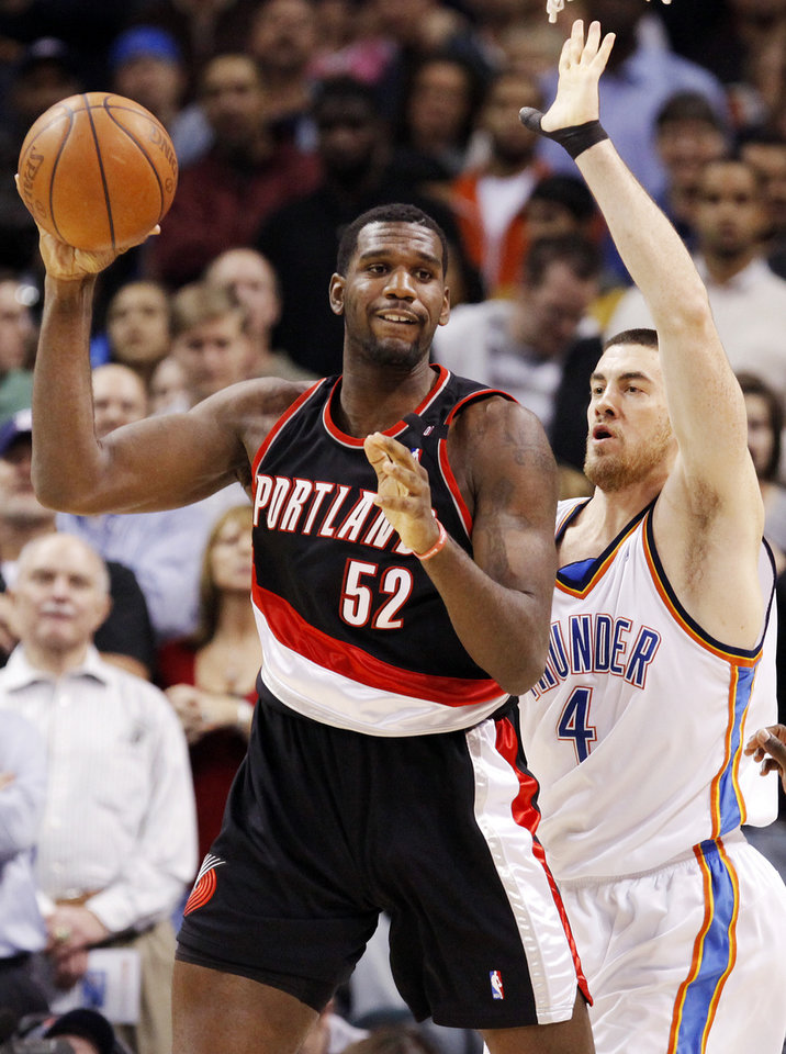 Photo - Portland's Greg Oden (52) looks to pass the ball away from the defense of Oklahoma City's Nick Collison (4) during the NBA basketball game between the Oklahoma City Thunder and the Portland Trail Blazers at the Ford Center in Oklahoma City, Friday, February 6, 2009. BY NATE BILLINGS, THE OKLAHOMAN ORG XMIT: KOD