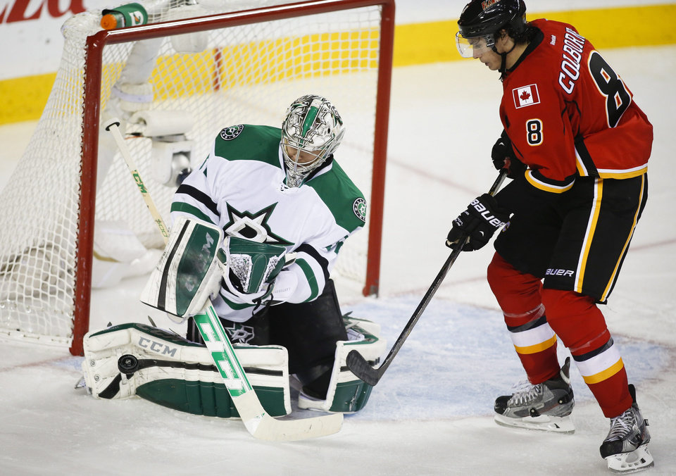 Photo - Dallas Stars goalie Kari Lehtonen, left, from Finland, kicks away a shot form Calgary Flames' Joe Colborne during third period NHL hockey action in Calgary, Alberta, Thursday, Nov. 14, 2013. The Dallas Stars beat the Calgary Flames 7-3. (AP Photo/The Canadian Press, Jeff McIntosh)