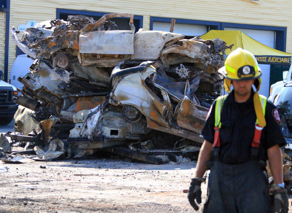 Photo - This photo provided by Surete du Quebec, emergency personnel look over the debris from a runaway train on Monday, July 8, 2013 in Lac-Megantic, Quebec, Canada.  A runaway train derailed igniting tanker cars carrying crude oil early Saturday, July 6.  At least thirteen people were confirmed dead and nearly 40 others were still missing in a catastrophe that raised questions about the safety of transporting oil by rail instead of pipeline.  (AP Photo/Surete du Quebec, The Canadian Press)